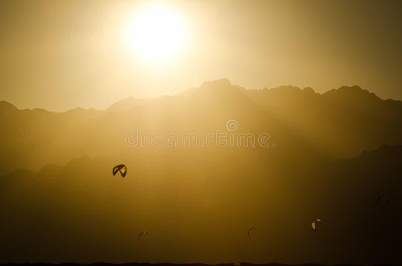 Cometas de kiteboarding en bahía durante puesta del sol sobre las montañas en Dahab, Sinaí, Egipto imagen de archivo libre de regalías