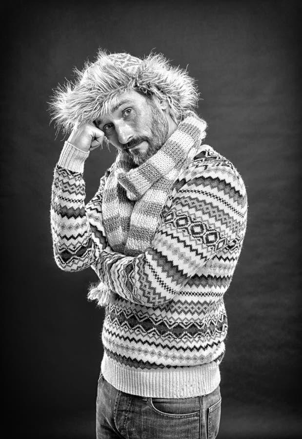 Comfort en warmte Bearded man die sweater met hoed en sjaal toegankelijk maakt Een winterensemble beschermt hem tegen kou royalty-vrije stock afbeelding