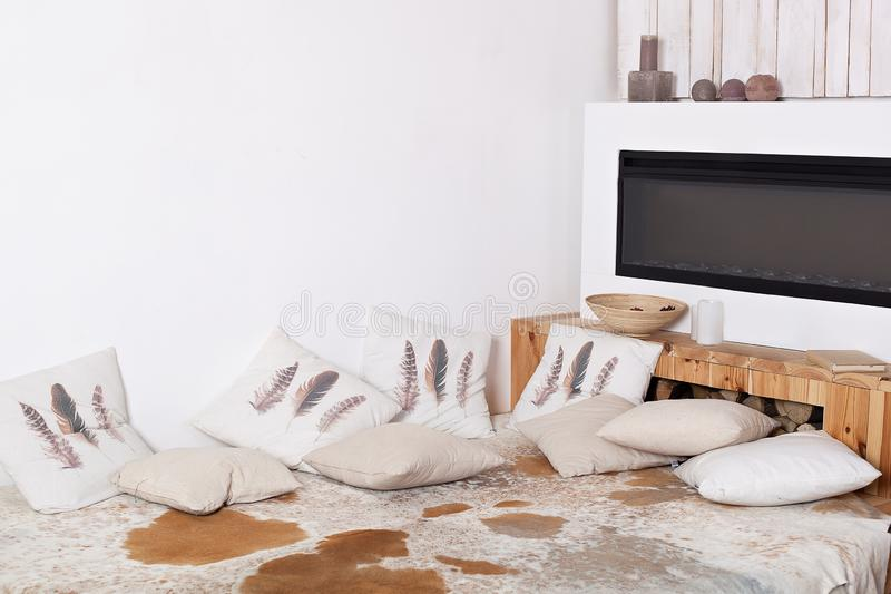 Comfort home. scandinavian interior with pillows. Modern country house interior with wooden bed, firewood, fireplace. Interior of stock images