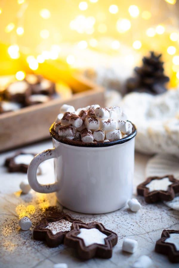 Comfort kerstvoedsel, mug van warme cacao met marshmallow en koekjes met luie lichten stock fotografie