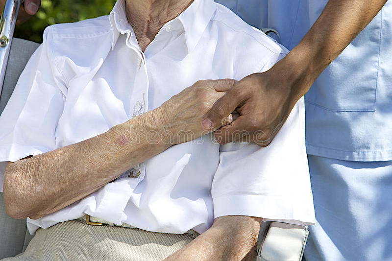Comfort and Support from a care giver towards the Elderly. Symbol of comfort and support from care giver to elderly women outdoor holding her hand royalty free stock image