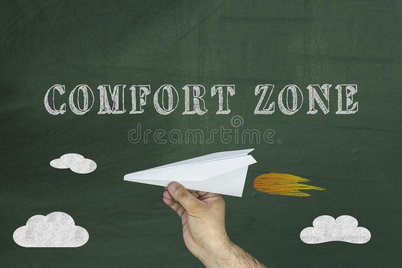 Comfort Zone Concept, Human hand holding paper airplane on chalkboard royalty free stock photo