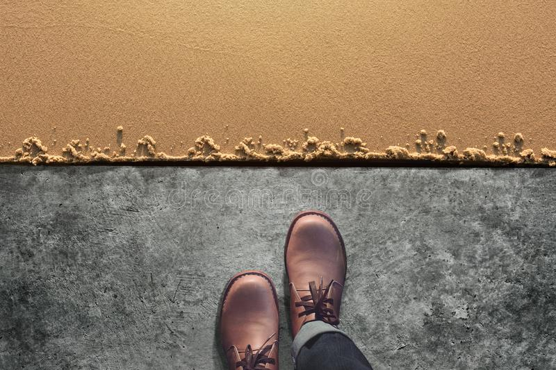 Comfort Zone Concept, Male with Leather Shoes Steps from Cement. Floor into Sand Beach. Top View royalty free stock photo
