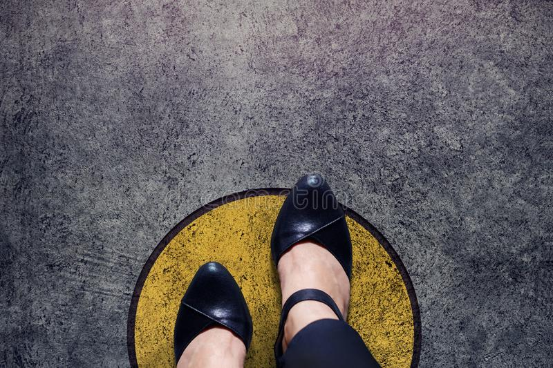 Comfort zone concept, woman with leather shoes steps over circle royalty free stock photo