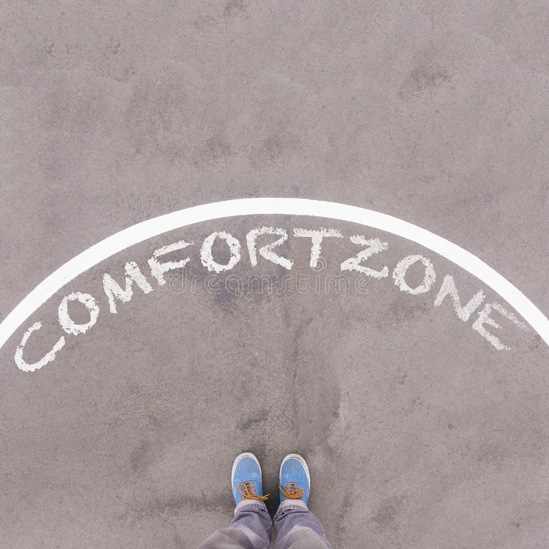 Comfort zone text on asphalt ground, feet and shoes on floor. Personal perspective footsie concept royalty free stock images