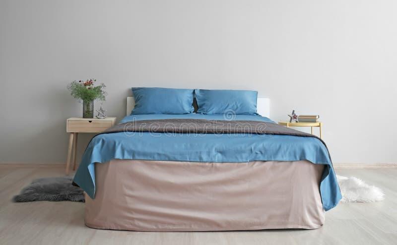 Comfortabel bed dichtbij lichte muur in ruimte royalty-vrije stock afbeeldingen