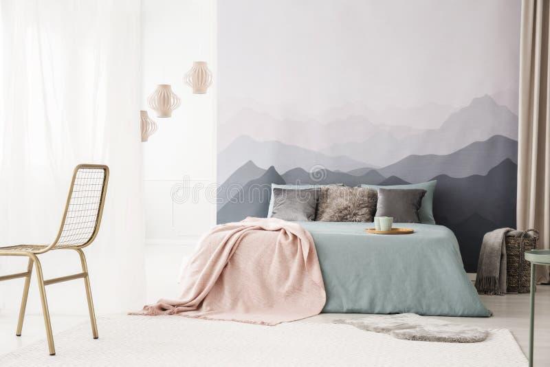 Comfortabel bed door landschapsbehang stock afbeeldingen