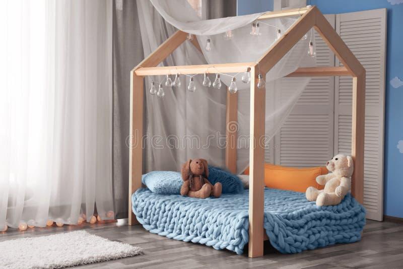 Comfortabel bed in kinderenruimte stock afbeelding
