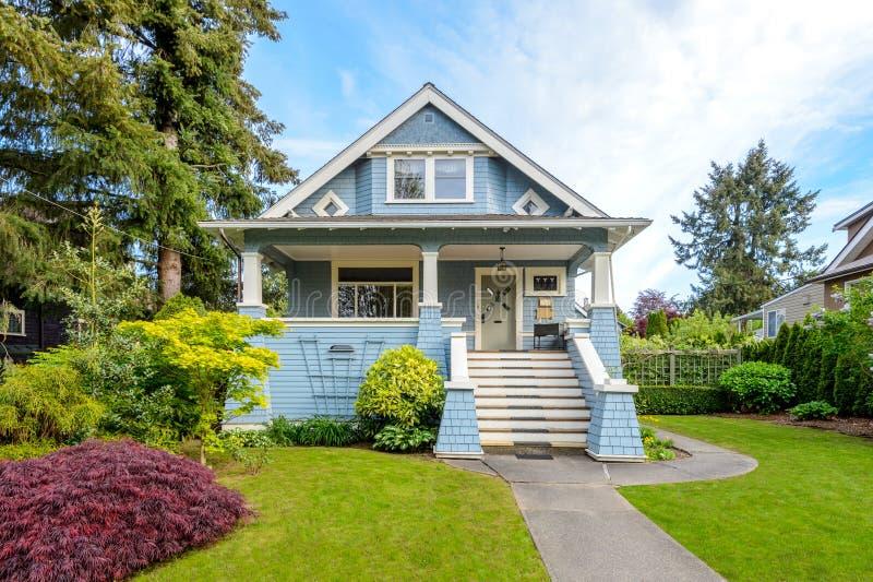 Comfortabel blauw huis met een mooie tuin op een zonnige dag stock foto