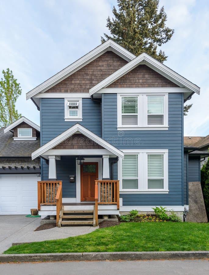 Comfortabel blauw huis op een zonnige dag stock afbeeldingen