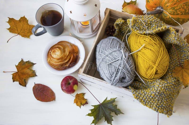 Comfortabel de herfstdecor met thee, kaneelbroodje, lantaarn, bladeren, knitt stock afbeeldingen