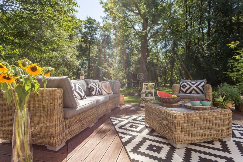 Comfortabel die terras door bomen wordt omringd stock foto