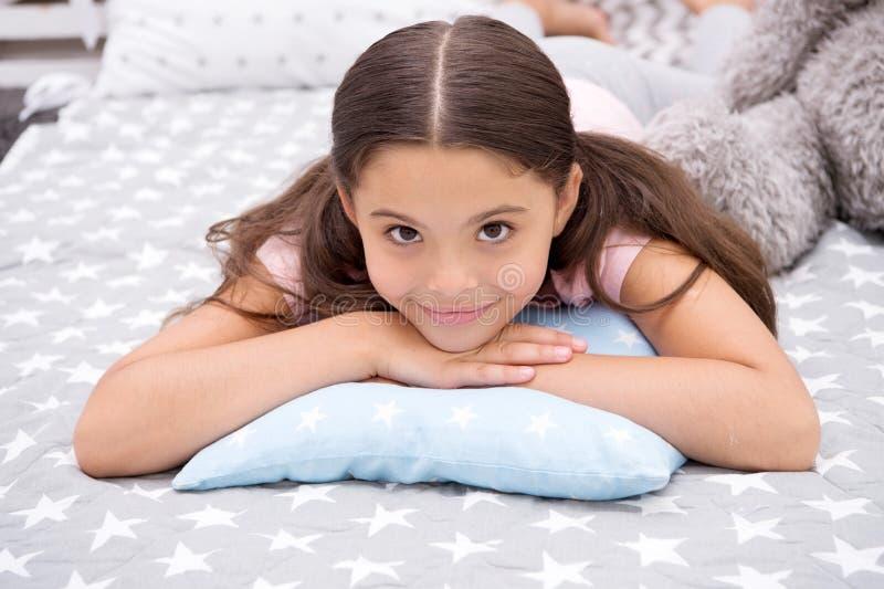 Comfortabel hoofdkussen Het meisje die gelukkig kind glimlachen legt op bed met de hoofdkussens van het sterpatroon en leuke plai stock afbeelding