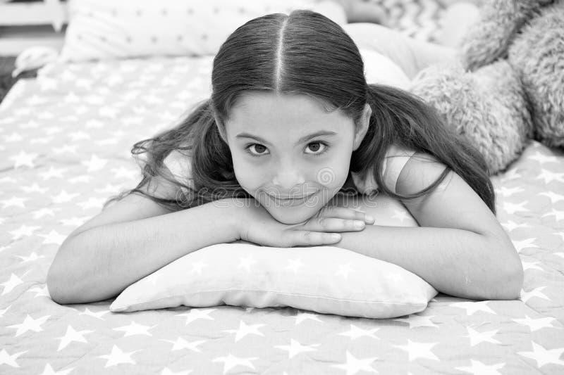 Comfortabel hoofdkussen Het meisje die gelukkig kind glimlachen legt op bed met de hoofdkussens van het sterpatroon en leuke plai stock fotografie