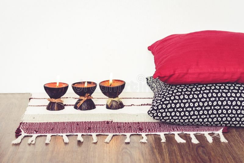 Comfortabel huis binnenlands decor, brandende kaarsen in kokosnotenshell op een multi-colored deken met decoratieve hoofdkussensa stock fotografie