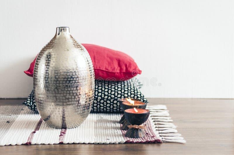Comfortabel huis binnenlands decor, brandende kaarsen in kokosnotenshell op een multi-colored deken met metaalvaas en decoratieve stock fotografie