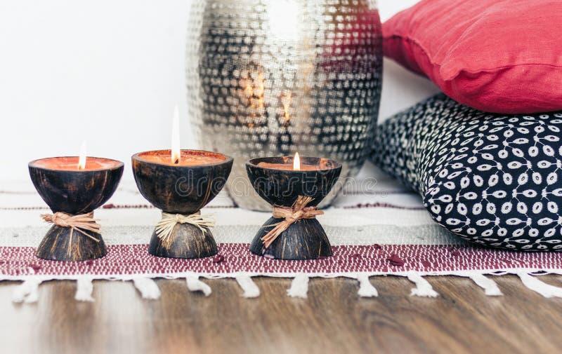 Comfortabel huis binnenlands decor, brandende kaarsen in kokosnotenshell op een multi-colored deken met metaalvaas en decoratieve royalty-vrije stock afbeeldingen