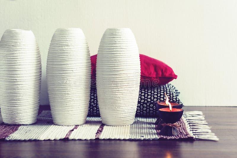 Comfortabel huis binnenlands decor, brandende kaarsen in kokosnotenshell op een multi-colored deken met witte ceramische vazen en stock afbeeldingen