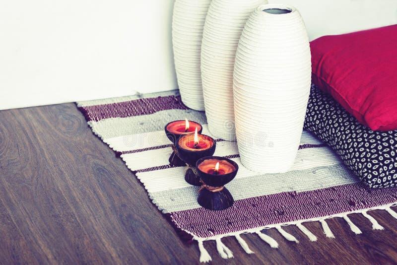 Comfortabel huis binnenlands decor, brandende kaarsen in kokosnotenshell op een multi-colored deken met witte ceramische vazen en royalty-vrije stock afbeeldingen