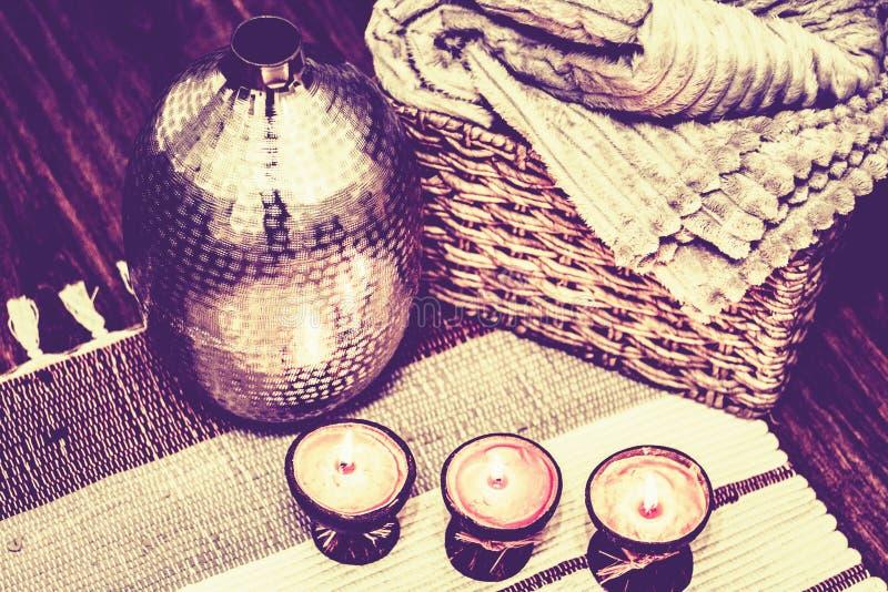 Comfortabel huis binnenlands decor, brandende kaarsen op een multi-colored deken op de achtergrond van een metaalvaas stock afbeeldingen