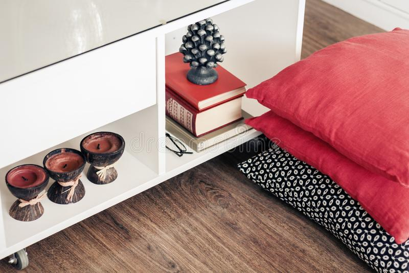 Comfortabel huis binnenlands decor, witte nightstand met stapel van boeken, kaarsen in kokosnotenshell met decoratieve hoofdkusse stock afbeelding