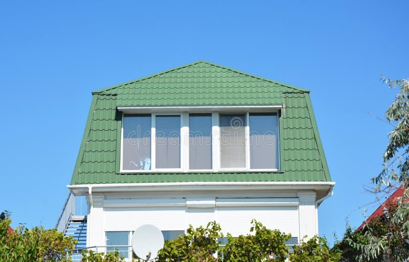 Comfortabel huis met mooie zoldermansard ruimte, grote vensters, en groen metaaldak royalty-vrije stock afbeeldingen