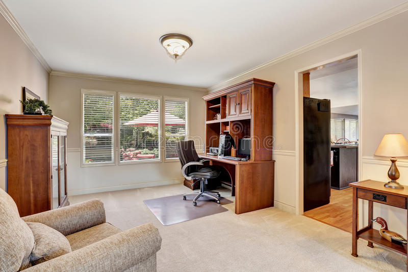 Comfortabel huisbureau met houten meubilair en tapijtvloer stock afbeeldingen
