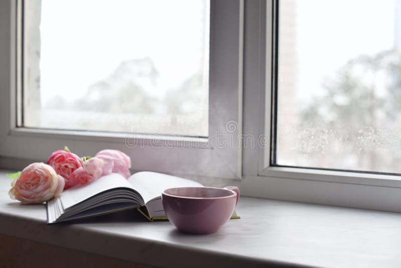 Comfortabel huisstilleven: kop van hete koffie, de lentebloemen en geopend boek met warme plaid op vensterbank tegen sneeuw royalty-vrije stock afbeeldingen