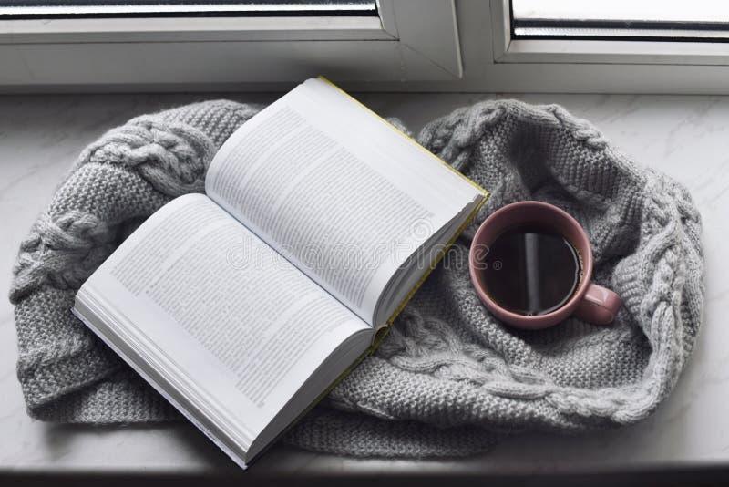 Comfortabel huisstilleven: kop van hete koffie en geopend boek met warme buiten plaid op vensterbank tegen sneeuwlandschap stock foto's