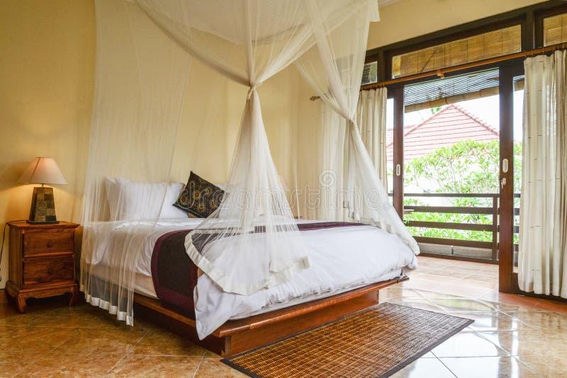 Comfortabel luifelbed in slaapkamer stock afbeeldingen