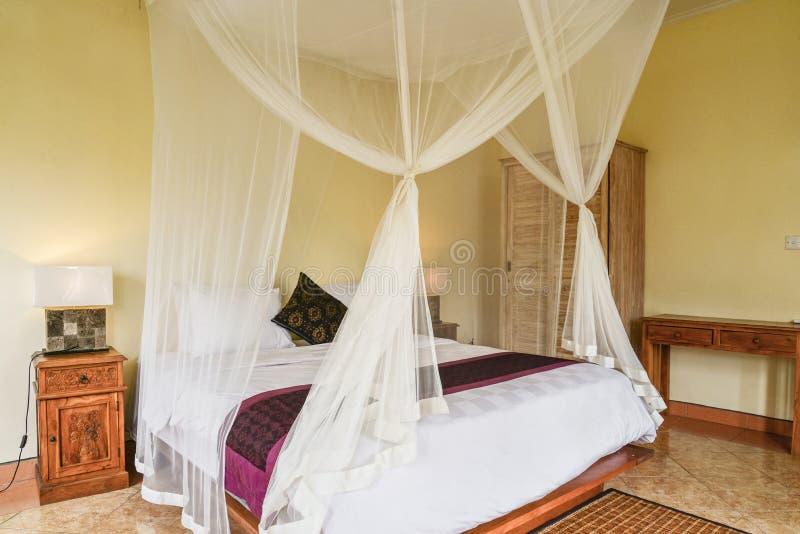 Comfortabel luifelbed in slaapkamer royalty-vrije stock foto's