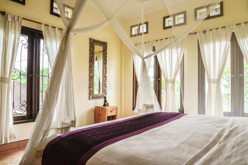 Comfortabel luifelbed in slaapkamer stock afbeelding