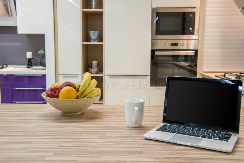 comfortabel modern keukenbinnenland met laptop en vruchten stock afbeeldingen