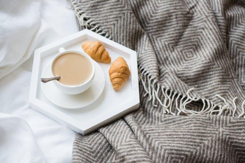 Comfortabel ontbijt in bed, kop van koffie en croissants op wit en stock foto