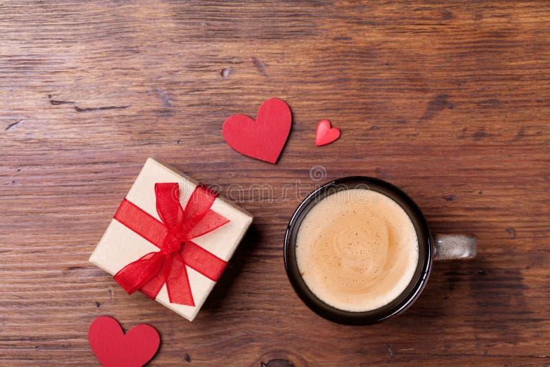 Comfortabel ontbijt voor Valentijnskaartendag Koffie, gift of huidig vakje en rode hart op de rustieke houten mening van de lijst stock afbeelding