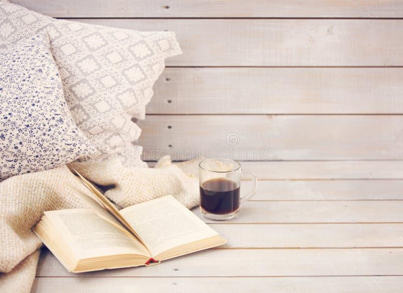 Comfortabel stilleven met boek, koffie, hoofdkussens en plaid stock afbeelding