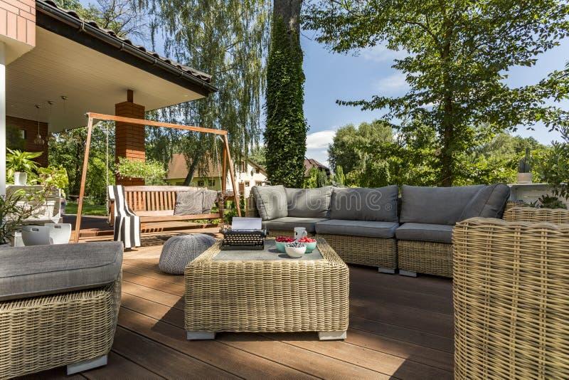 Comfortabel terras met rieten meubilair stock afbeeldingen