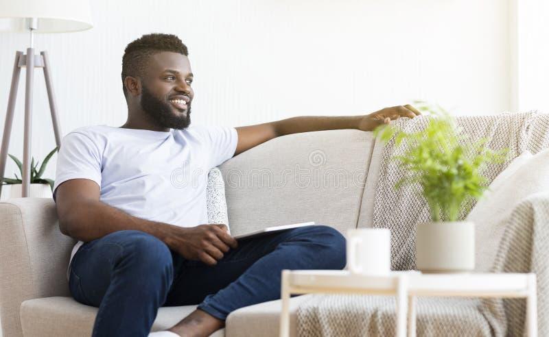 Comfortabel weekend Vreedzame Afrikaanse mens die thuis rust stock fotografie