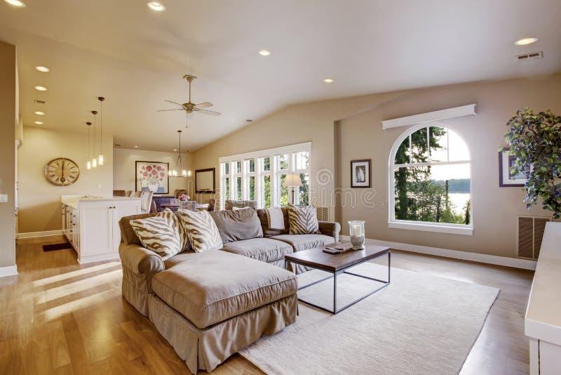 Comfortabel woonkamer en eetkamerbinnenland in beige tonen met gewelfde plafond en hardhoutvloer stock fotografie