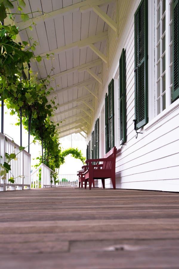 Comfortabele behandelde houten galerij met druiven en banken stock fotografie