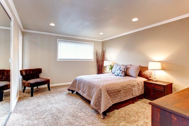 Comfortabele bruine tonenslaapkamer met houten meubilair en zacht tapijt stock foto's