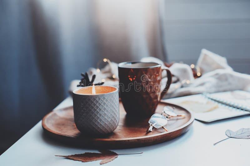 comfortabele de herfst of de winterochtend thuis Stillevendetails met kop thee, kaars, schetsboek met herbarium en warme sweater royalty-vrije stock fotografie
