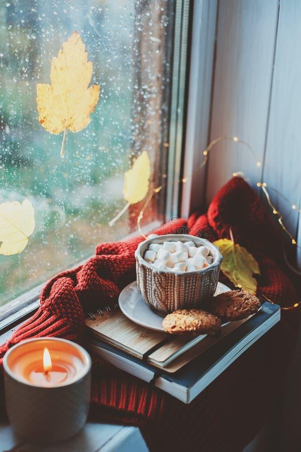 Comfortabele de herfstochtend thuis Hete cacao met heemst en kaars op venster in regenachtige koude dag stock fotografie