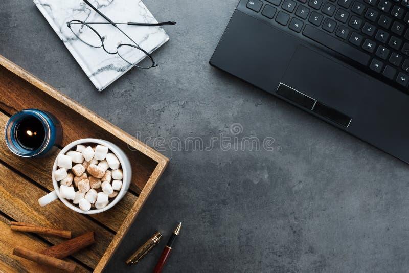 Comfortabele de winter bedrijfs flatlay regeling met zwarte laptop, houten dienblad met veganistcacao royalty-vrije stock afbeeldingen