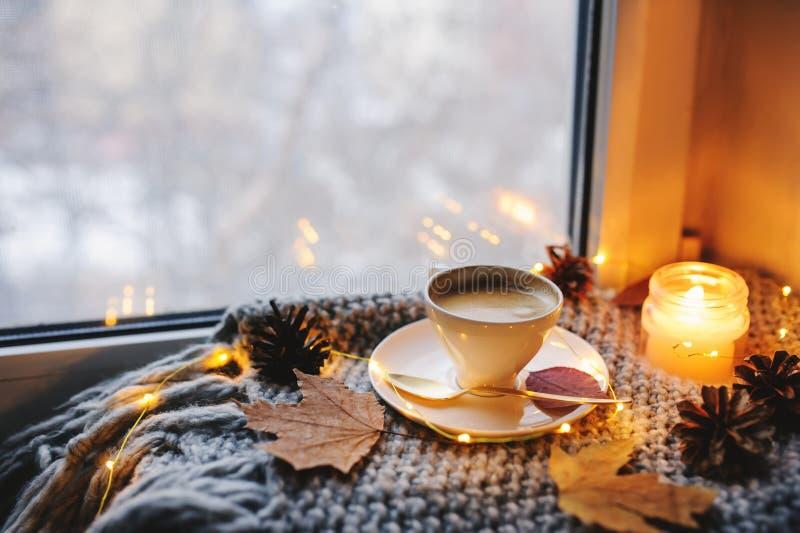 Comfortabele de winter of de herfstochtend thuis Hete koffie met gouden metaallepel, warme deken, slinger en kaarslichten royalty-vrije stock fotografie