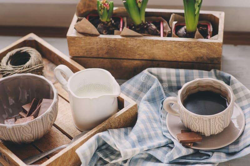 Comfortabele de winterochtend thuis Koffie, melk en chocolade op houten dienblad Huacinthbloemen op achtergrond Warme stemming royalty-vrije stock fotografie
