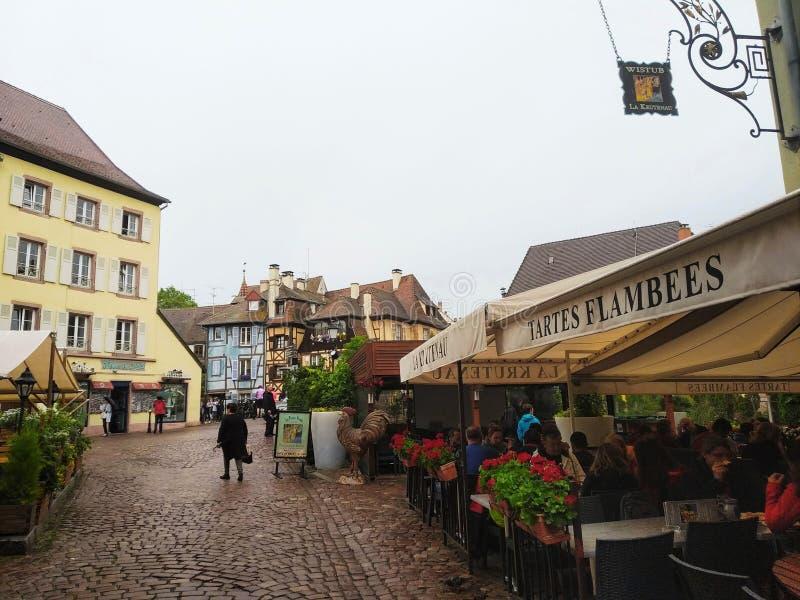 Comfortabele die restaurants met bloemen en huizen met kleurrijke voorgevels in de straten van Colmar worden verfraaid stock foto's