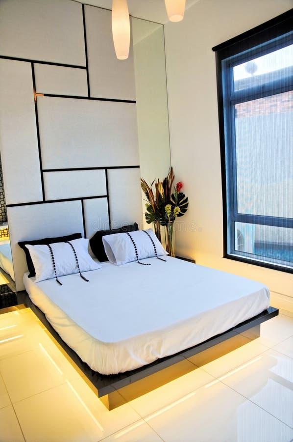 Comfortabele en goed geleverde slaapkamer stock afbeelding
