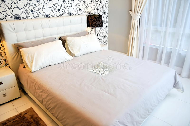 Comfortabele en goed geleverde slaapkamer stock foto