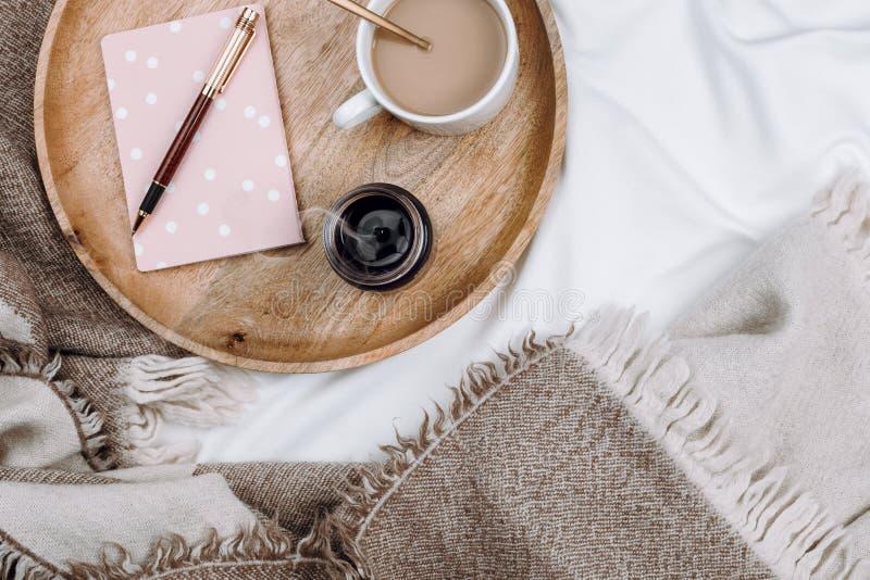 Comfortabele flatlay met houten dienblad, kop van koffie of cacao, kaars, notitieboekjes stock foto's